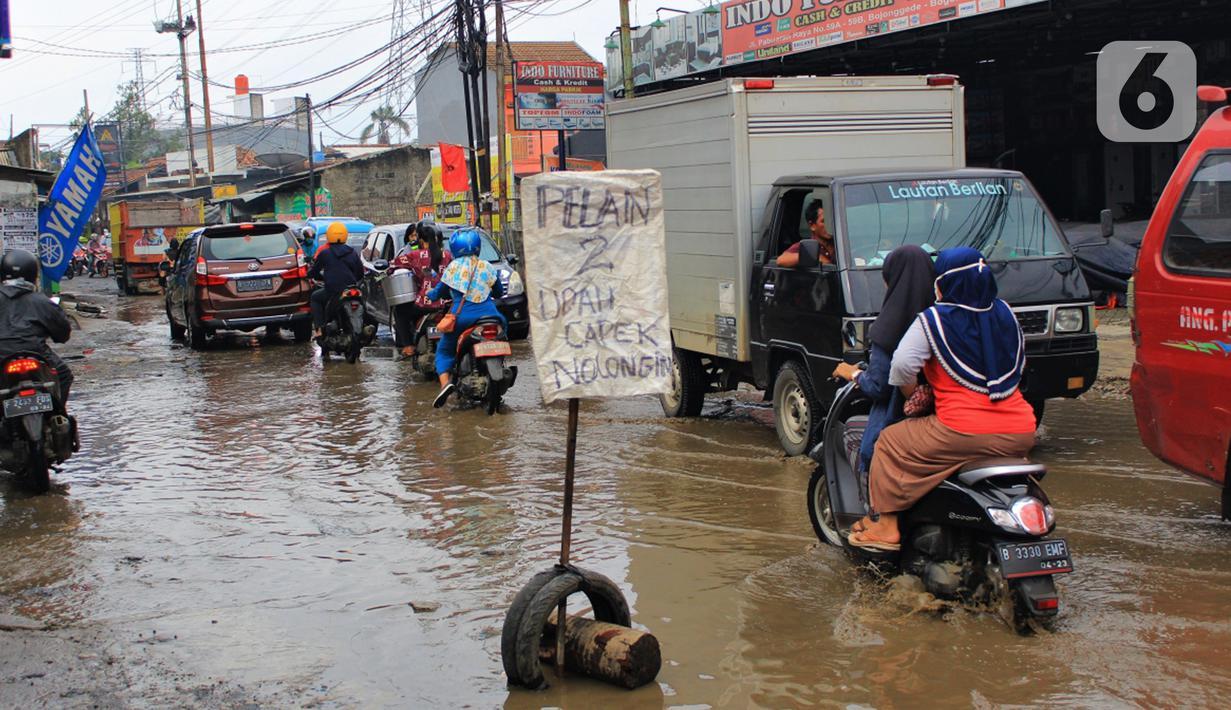 Kondisi jalan berlubang dan tergenang air di Jalan Raya Pabuaran, Citayam, Depok, Rabu (26/2/2020). Kerusakan disebabkan oleh kubangan air yang menggenangi jalan tersebut pada musim hujan  yang melanda Jabodetabek dua bulan terakhir. (merdeka.com/magang/Muhammad Fayyadh)