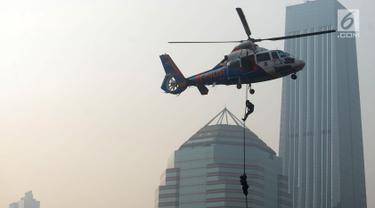 Petugas kepolisian menuruni helikopter menggunakan tali dalam apel pengamanan Asian Games 2018 di Lapangan Ditlantas Polda Metro Jaya, Jakarta, Selasa (31/7). Apel juga diikuti oleh TNI dan instansi terkait. (Merdeka.com/Imam Buhori)