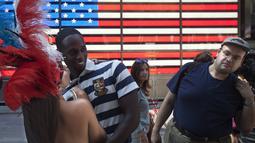 Seorang wanita berpose bersama seorang wisatawan dipinggiran ruas jalan Times Square, New York,AS,  Selasa (18/8/2015). Mereka meminta uang kepada para wisatawan yang ingin mengajak foto bersama dengan tanpa memakai busana. (REUTERS/Carlo Allegri)