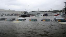Sejumlah mobil terendam banjir di sebuah dealer setelah badai Harvey menerjang di Dickinson, Texas, Minggu (27/8). Badai Harvey menghantam Texas pada Jumat malam dengan hujan deras dan angin berkecepatan 215 kilometer per jam. (AP Photo)
