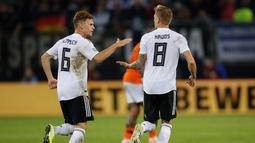Gelandang Jerman Toni Kroos (kanan) berselebrasi usai mencetak gol ke gawang Belanda pada pertandingan grup C  kualifikasi Euro 2020 di Hamburg, Jerman (6/9/2019). Belanda menang telak 4-2 atas Jerman. (AFP Photo/Odd Andersen)