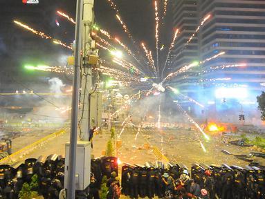 Petugas kepolisian menghalau tembakan kembang api saat bentrokan dengan massa aksi 22 Mei di sekitar depan gedung Bawaslu, Jalan MH Thamrin, Jakarta, Rabu (22/5/2019). Aksi unjuk rasa itu dilakukan menyikapi putusan hasil rekapitulasi nasional Pemilu serentak 2019. (Liputan6.com/Angga Yuniar)