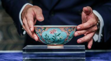 Wakil Kepala Sotheby Asia, Nicolas Chow memegang mangkuk langka dari masa Dinasti Qing pada pratinjau media di Hong Kong, Selasa (3/4). Mangkuk antik kepunyaan Kaisar Kangxi itu terjual dengan harga USD 30,4 juta (Rp 417 miliar). (ISAAC LAWRENCE/AFP)