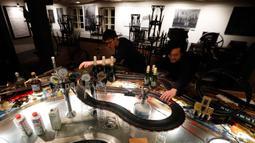 Pekerja menghabiskan waktu dengan bermain lintasan mobil balap mainan yang dipasang di sebuah bar di Praha, Republik Ceko, 15 Oktober 2020. Area bar menjadi lintasan mobil mainan yang bisa dimanfaatkan para karyawan untuk mengusir kebosanan saat menunggu pesanan. (AP Photo/Petr David Josek)