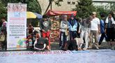 Pengunjung membubuhkan tanda tangan di atas spanduk raksasa saat car free day (CFD) di Bundaran HI, Jakarta, Minggu (22/7). Aksi ini merupakan dukungan masyarakat untuk kesuksesan pelaksanaan Asian Games 2018. (Merdeka.com/Iqbal Nugroho)