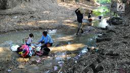 Warga mencuci pakaian dengan air dari lubang pada aliran Sungai Cihoe yang digunakan untuk memenuhi kebutuhan sehari-hari di Ridogalih, Cibarusah, Bekasi, Minggu (7/7/2019). Sudah lebih dari dua bulan, warga memanfaatkan sisa aliran sungai yang kotor akibat musim kemarau. (merdeka.com/Arie Basuki)