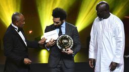 Presiden Konfederasi Sepak Bola Afrika (CAF) Ahmad Ahmad memberikan penghargaan Pemain Terbaik Afrika 2018 kepada bintang Liverpool, Mohamed Salah dalam malam penghargaan di Dakar, Senegal, Selasa (8/1). (SEYLLOU/AFP)