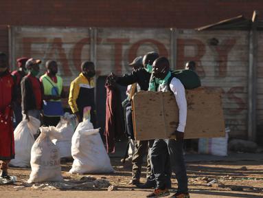 Orang-orang menunggu tumpangan di terminal bus di Harare, Zimbabwe (22/7/2020). Presiden Zimbabwe Emmerson Mnangagwa mengumumkan sederet kebijakan karantina lockdown, termasuk penerapan jam malam mulai pukul 18.00-06.00 waktu setempat, guna meredam lonjakan kasus COVID-19. (Xinhua/Shaun Jusa)
