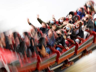 Pengunjung menaiki wahana Stealth di taman hiburan Thorpe Park, Chertsey, barat daya London, Inggris, Senin (12/4/2021). Inggris melonggarkan pembatasan terkait virus corona COVID-19. (Photo by Adrian DENNIS/AFP)