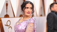 Aktris Salma Hayek ikut ambil bagian pada malam penghargaan Piala Oscar 2018 di Dolby Theatre, Los Angeles, Minggu (4/3). Gaun Salma Hayek tersebut dipercantik dengan berlian yang menjuntai dari bagian bahu. (Christopher Polk/GETTY IMAGES/AFP)