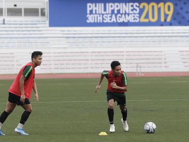 Pemain Timnas Indonesia U-22, Syarian Abimanyu dan Evan Dimas, bersiap melakukan tendangan bebas saat latihan di Stadion Rizal Memorial, Manila, Senin (25/11). Latihan ini persiapan jelang laga SEA Games 2019 melawan Thailand. (Bola.com/M Iqbal Ichsan)