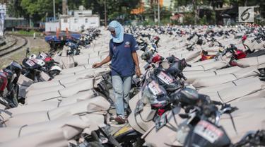 Pekerja melewati motor pemudik sebelum dikirim dengan kereta api di Stasiun Jakarta Gudang, Selasa (28/5/2019). Direktorat Lalu Lintas dan Angkutan Kereta Api Kementerian Perhubungan mengangkut 18.096 motor pemudik secara gratis pada mudik Lebaran 2019. (Liputan6.com/Faizal Fanani)