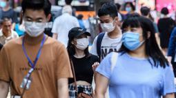 Pejalan kaki mengenakan masker sebagai tindakan pencegahan Covid-19 saat berjalan di Hong Kong (13/5/2020). Dua orang di Hong Kong dinyatakan positif Covid-19, mengakhiri perjalanan 24 hari tanpa kasus baru yang mulai melonggarkan peraturan jarak sosial. (AFP/Anthony Wallace)