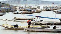 Seorang nelayan memindahkan perahunya melewati jajaran perahu, mendekati pantai perkampungan nelayan, tak jauh dari jembatan Suramadu, di Nambangan Kenjeran Surabaya. (Antara)