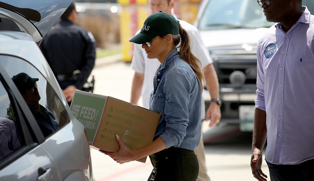 Ibu negara AS, Melania Trump membawa barang untuk disumbangkan kepada korban Badai Harvey saat berkunjung ke First Church, Pearland, Texas (2/9).  Melania tampil kasual dengan mengenakan kemeja jeans dan sepatu sneakers. (Win McNamee/Getty Images/AFP)