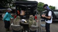 Petugas Satpol PP mendata warga yang terjaring razia protokol kesehatan COVID-19 di Kebon Nanas, Jakarta, Selasa (15/6/2021). Saat kasus positif Covid-19 di Jakarta meningkat, masih banyak warga yang belum menjalankan protokol kesehatan, salah satunya mengenakan masker. (merdeka.com/Imam Buhori)
