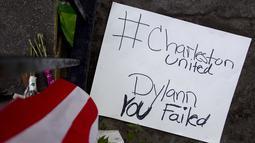 Sebuah tulisan di letakkan di luar Gereja Emanuel, Charleston, Amerika Serikat, Minggu (21/6/2015). Gereja tersebut dibuka kembali untuk ratusan jemaat yang berkabung usai penembakan yang menewaskan 9 orang. (REUTERS/Carlo Allegri)
