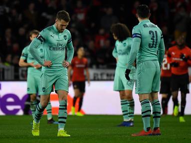 Ekspresi kecewa Aaron Ramsey pada leg 1, babak 16 besar Liga Europa yang berlangsung di Stadion Roazhon Park, Rennes, Jumat (8/3). Arsenal kalah 1-3 kontra Rennes. (AFP/Damien Meyer)
