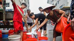 Warga mengisi wadah mereka dengan air dari truk tangki pasokan pemerintah di Hanoi, Vietnam, Kamis (17/10/2019). Pejabat tinggi pemerintah mengonfirmasi bahwa air ledeng di Hanoi tenggara terkontaminasi dengan styrene, suatu zat karsinogenik. (Nhac NGUYEN/AFP)