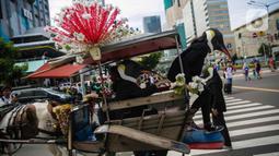 Aktivis Greenpeace turun dari kereta kuda mengenakan topeng penguin saat menggelar aksi dalam car free day di kawasan Thamrin, Jakarta, Minggu (9/2/2020). Mereka mengajak pemerintah untuk berpartisipasi dalam mewujudkan Perjanjian Laut Internasional (Global Ocean Treaty). (Liputan6.com/FaizalFanani)
