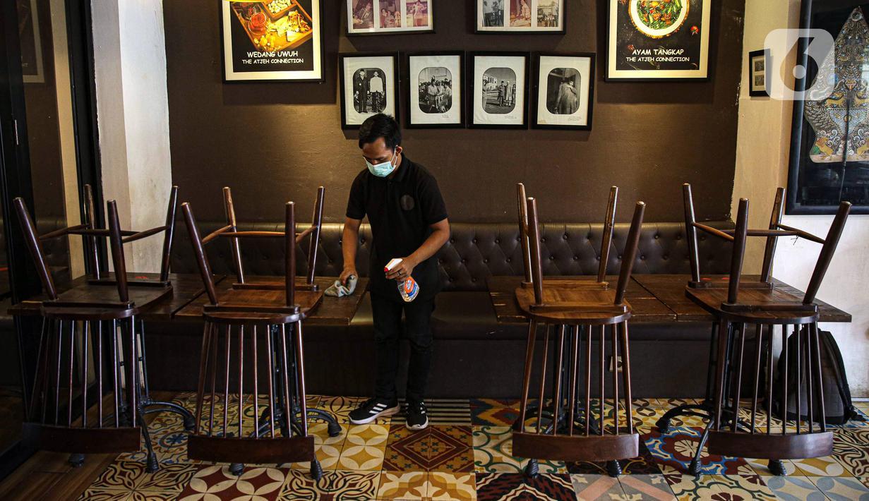 Pekerja mengelap meja di salah satu restoran di Jakarta, Kamis (29/7/2021). Kepala Dinas Pariwisata dan Ekonomi Kreatif (Disparekraf) DKI Jakarta Gumilar Ekalaya mengatakan, Pemprov DKI Jakarta akan mewajibkan pengunjung salon dan restoran sudah divaksin COVID-19. (Liputan6.com/Faizal Fanani)