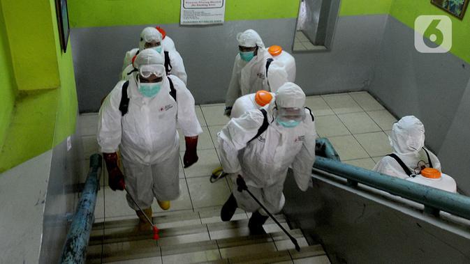 Petugas Palang Merah Indonesia (PMI) melakukan penyemprotan disinfektan di SMPN 216 Jakarta, Senin (16/3/2020). Mulai hari ini, aktivitas sekolah di sejumlah wilayah Indonesia diliburkan untuk mengantisipasi penyebaran virus corona COVID-19. (merdeka.com/Arie Basuki)