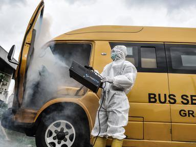 Petugas Kebersihan Bus (PKB) melakukan pengasapan antibakteri pada bus sekolah di Pool Unit Pelayanan Angkutan Sekolah (UPAS) DKI Jakarta, Kramat Jati, Selasa (5/1/2021). Sterilisasi bus sekolah dilakukan usai digunakan mengangkut pasien terpapar Covid-19 ke RS rujukan. (merdeka.com/Iqbal Nugroho)