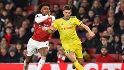 Duel antara Alex Iwoby dan Aleksey Rios pada leg 2, babak 16 besar Liga Europa yang berlangsung di stadion Emirates, London, Jumat (22/2). Arsenal menang 3-0 atas Bate Borisov. (AFP/Glyn Kirk)