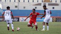 Pergerakan bek Persis, Wirabuana Prayogo (merah), saat dikepung dua pemain Madura FC dalam laga di Stadion Wilis, Madiun, Rabu (18/9/2019). (Bola.com/Vincentius Atmaj
