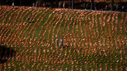 Orang-orang berjalan di antara bendera Spanyol untuk mengenang korban COVID-19 di Madrid, Minggu (27/9/2020). Asosiasi keluarga korban virus corona memasang 53.000 bendera kecil Spanyol di sebuah taman Madrid untuk menghormati mereka yang meninggal akibat pandemi. (AP Photo/Manu Fernandez)
