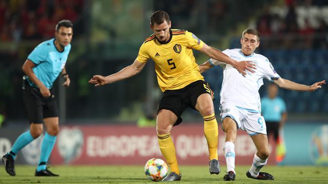 Bek Belgia, Jan Vertonghen, berebut bola dengan gelandang San Marino, Marcello Mularoni, pada laga Kualifikasi Piala Dunia 2022 di Olympic Stadium, Serravalle, Jumat (6/9). San Marino kalah 0-4 dari Belgia. (AFP/Isabella Bonotto)
