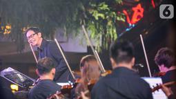 Konduktor Addie MS membawakan orchestra bertema Symphony Under the Stars: Movie Fest II di Lippo Mall Kemang, Jakarta, Sabtu (26/10/2019). Addie MS bersama  48 musisi Twilite Orchestra  membawakan soundtrack dari film Indonesia maupun mancanegara. (Liputan6.com/Fery Pradolo)