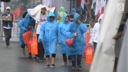 Pendukung capres nomor urut 01 Joko Widodo diguyur hujan saat tiba di Sentul International Convention Center, Bogor, Jawa Barat, Minggu (24/2). Jokowi bakal menyampaikan pidato politik di hadapan 40.000 pendukungnya. (Liputan6.com/Herman Zakharia)