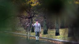 Seorang penggemar sepeda mengenakan kostum sejarah sambil menuntun Penny Farthing atau dikenal sebagai sepeda roda tinggi selama kompetisi tradisonal 'One Mile Race' di Praha, Republik Ceko pada 3 November 2018. (Photo by Michal CIZEK / AFP)