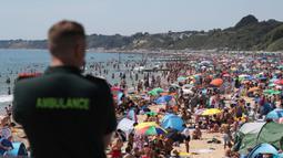 Petugas layanan ambulans memandangi kerumunan pengunjung yang berkumpul di pantai di Bournemouth, Kamis (25/6/2020). Pantai tersebut diserbu warga Inggris, setelah masa pelonggaran pembatasan sosial akibat covid-19 dan pembatasan perjalanan Eropa. (Andrew Matthews/PA via AP)