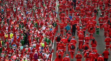 Orang-orang mengenakan kostum Sinterklas ambil bagian dalam Santa Claus Run di Madrid, Spanyol, Minggu (9/12). Ribuan orang berjalan dan berlari dalam perlombaan Santa tahunan melintasi jalan-jalan ibu kota Spanyol. (Gabriel BOUYS / AFP)
