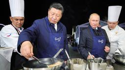 Aksi Presiden Rusia Vladimir Putin (dua kanan) dan Presiden China Xi Jinping (kedua kiri) saat membuat pancake bersama di sela acara Eastern Economic Forum di Vladivostok, Rusia, Selasa (11/9). (Sergei Bobylev/TASS News Agency Pool Photo via AP)