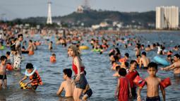 Pengunjung pantai setempat menikmati berenang di pantai Bai Chay di kota Ha Long provinsi timur laut Quang Ninh (16/5/2020). Seiring dengan meredanya virus corona dan otoritas setempat melonggarkan pembatasan perjalanan, pantai Bai Chay kembali didatangi ratusan wisatawan. (AFP/Manan Vatsyayana)