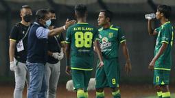 Pelatih Persebaya Surabaya, Aji Santoso memberi arahan kepada para pemainnya saat menghadapi Persik Kediri dalam laga Grup C Piala Menpora 2021 di Stadion Si Jalak Harupat, Bandung, Selasa (23/3/2021). Persebaya menang 2-1 atas Persik. (Bola.com/M Iqbal Ichsan)