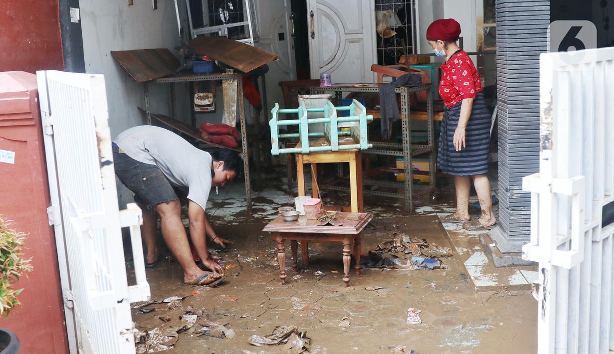 Warga membersihkan lumpur sisa banjir di halaman rumahnya di perumahan Ciledug Indah, Tangerang, Senin (21/2/2021). Banjir yang menggenangi perumahan tersebut membuat warga mengalami kerugian cukup besar karena barang-barang berharga mereka rusak parah. (Liputan6.com/Angga Yuniar)