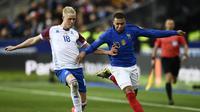 Kylian Mbappe mencoba melewati Hordur Magnusson pada laga kedua Kualifikasi Piala Eropa 2020 Grup H yang berlangsung di Stadion Stade de France, Paris, Selasa (26/3). Perancis menang 4-0 atas Islandia. (AFP/Martin Bureau)