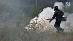 Petugas dari Puskesmas Kecamatan Cengkareng melakukan pengasapan (fogging) untuk membasmi nyamuk Demam Berdarah di Kawasan Kedaung, Jakarta Barat, Selasa (23/4). Pengasapan (fogging) bertujuan untuk membunuh nyamuk dewasa. (merdeka.com/Imam Buhori)