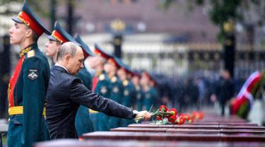 Presiden Rusia, Vladimir Putin meletakkan bunga di tengah hujan lebat saat upacara kehormatan untuk memperingati invasi Nazi Jerman pada 1941 di Benteng Kremlin, Moskow, Kamis (22/6). (Alexei Druzhinin/Sputnik, Kremlin Pool Photo via AP)