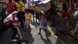 Seorang wanita memberi uang saat anak-anak melakukan tarian singa dengan kepala singa yang terbuat dari kardus saat menghibur pejalan kaki  untuk menyambut Tahun Baru Imlek di Manila (4/2). (AFP Photo/Ted Aljibe)