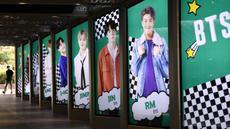 """Warga melewati poster komersial anggota boyband K-pop, BTS, di luar toko bebas pajak di Seoul, Selasa (1/9/2020). Lagu """"Dynamite"""" puncaki tangga lagu Billboard dan membuat BTS menjadi penyanyi Kpop sekaligus grup Asia pertama yang meraih posisi nomor satu di Billboard Hot 100. (Jung Yeon-je/AFP)"""