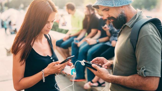 Ilustrasi: Mengisi daya smartphone dengan powerbank (Sumber: Istock/ Getty Images)