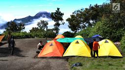 Pendaki mendirikan tenda dengan pemandangan Gunung Merapi dari atas Gunung Merbabu di Selo, Jawa Tengah, Sabtu (2/2/2019). Aktivitas Gunung Merapi dalam beberapa hari terakhir masih tinggi dan masih berada di level 2 atau waspada. (Merdeka/Arie Basuki)