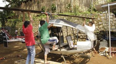 Gambar yang diambil pada 17 November 2019, Jujun Junaedi (kanan) menyelesaikan pembuatan helikopter buatannya di halaman belakang rumahnya di Sukabumi. Jujun yang berusia 41 tahun ini menargetkan helikopter berbahan bakar bensinnya rakitannya dapat diuji terbang pada akhir 2019. (Wulung WIDARBA/AFP)