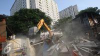 Alat berat merobohkan bangunan di kawasam Rawajati, Jakarta, Kamis (1/9). Penertiban puluhan bangunan liar di kawasan tersebut menyebabkan warga terpaksa menyelamatkan barang berharga mereka ke tepi rel kereta api. (Liputan6.com/Immanuel Antonius)