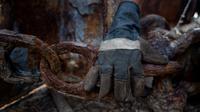 Pekerja memegang rantai berkarat di tempat pemotongan kapal tua di Cilincing, Jakarta, Kamis (13/2/2020). Proses daur ulang ini dilakukan dengan cara memotong kapal menjadi bagian-bagian kecil yang kemudian dijual sebagai besi tua. (Xinhua/Agung Kuncahya B.)